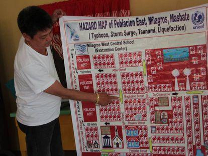 El líder del 'barangay' de Poblacion East, Joseleo O. Tan, muestra el plan de evacuación de la zona, en Milagros (Filipinas).