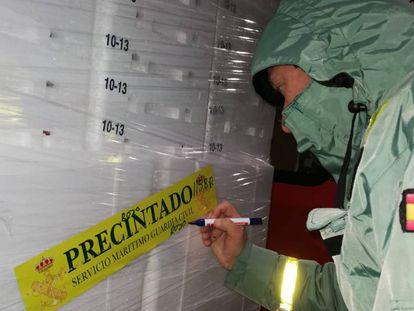 Un agente del Servicio Marítimo precinta una de las partidas de cigalas intervenidas en la Operación Pinza Roja.