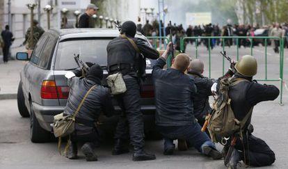 Un grupo de prorrusos armados se cubren tras un coche cerca de la sede de la policía de Luhansk.