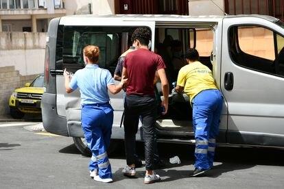 Dos trabajadores acompañan a uno de los menores marroquíes a las puertas del juzgado de Ceuta  después de que se paralizara este lunes su repatriación.