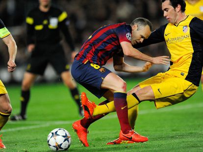 Iniesta y Godín luchan por el balón.