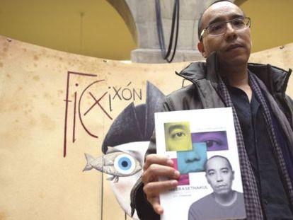 El director y guionista tailandés posa con un ejemplar del libro sobre su obra.
