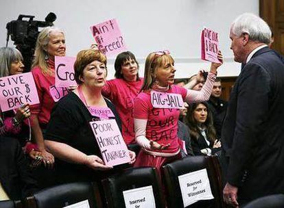 El consejero delegado de AIG, Edward Liddy, ante unas mujeres que protestaban por las primas poco antes de que interviniera en el Congreso.