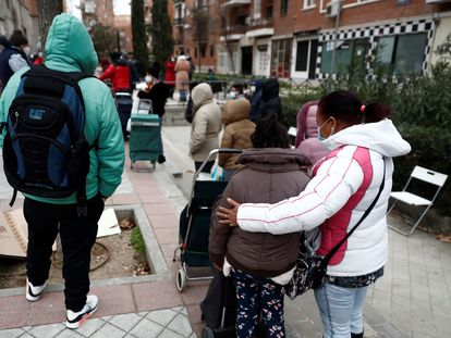 Una mujer y una niña esperan su turno para recoger alimentos de una ONG, el pasado enero en Madrid.