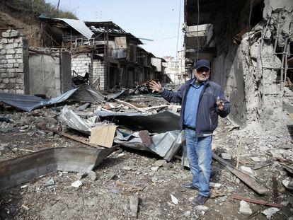 Un hombre muestra el edificio donde vivía en Stepanakert, destruido por artillería de Azerbaiyán, este sábado en Nagorno Karabaj.