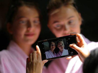 Dos modelos posan para una fotografía tomada con un móvil.