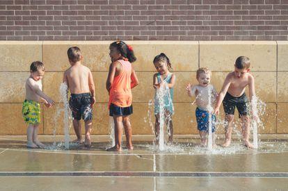 Un grupo de niños juega en una fuente.