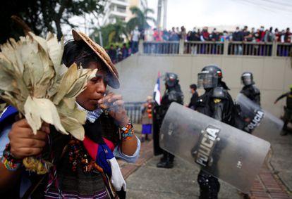 Un indígena lleva a cabo un ritual junto a las autoridades que tratan de dispersar a manifestantes en Cali, el pasado 28 de abril.