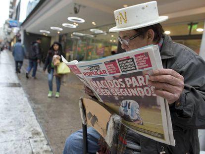 Un limpiabotas lee una portada que refleja la derrota argentina ante Chile.