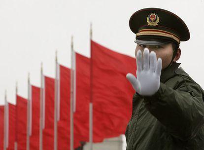 Un soldado que hace guardia en la plaza de Tiananmen gesticula ante los fotógrafos.