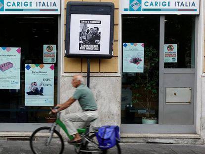 Un hombre pedalea en una bicicleta junto a una sucursal de la Banca Carige en Roma