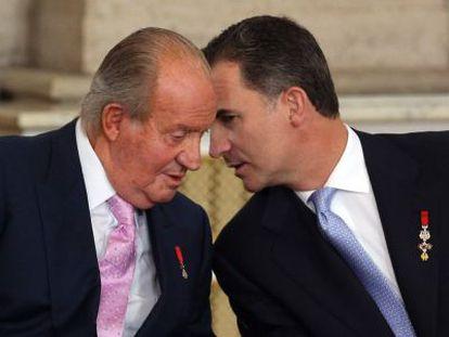Juan Carlos I con su hijo, Felipe VI, el 18 de junio de 2014, en el acto de sanción de la ley de abdicación en el palacio Real.