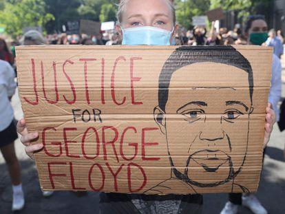 Una manifestante sujeta una pancarta que pide justicia para George Floyd.