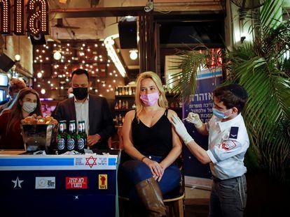 Una mujer recibe la vacuna  el pasado 18 de febrero dentro de una campaña del Ayuntamiento de Tel Aviv, que ofrece una bebida gratis a quien se vacune.