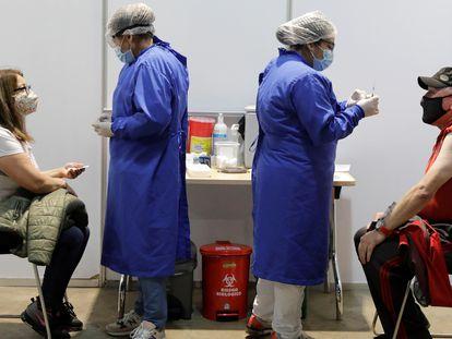 Dos personas reciben la vacuna contra la covid-19 en el centro de vacunación más grande de Colombia.