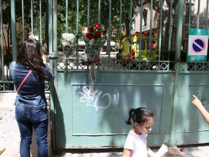 Padres de alumnos colocan flores en la verja del colegio.