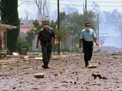 Tres policías caminan por una calle en Río Tercero (Argentina), tras la explosión en noviembre de 1995.