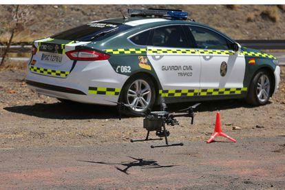 Arriba, un dron de la DGT delante de un coche de la Guardia Civil.