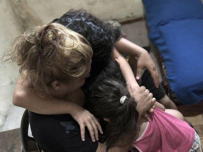 Una madre libanesa abraza a sus tres hijos en su casa de Beirut el 11 de agosto de 2020, unos días después de la explosión de más de dos toneladas de nitrato de amonio en el puerto de la capital libanesa, una de las peores tragedias en este país.