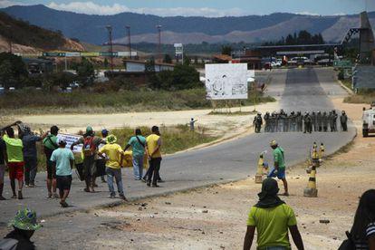 Manifestantes antichavistas frente a una barrera de guardias nacionales en la frontera entre Venezuela y Brasil.