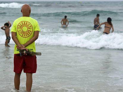 FOTO: Un socorrista vigila la playa de Punta Prima, en el municipio de Sant Lluís en Menorca. / VÍDEO: Los ahogamientos aumentan.