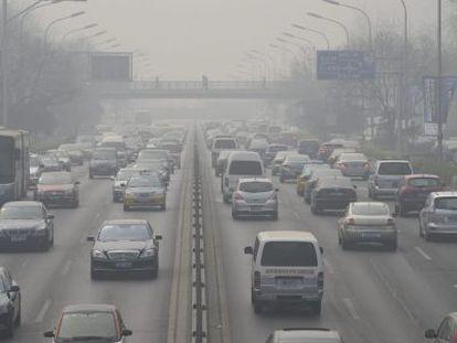 Vista de una carretera cubierta por una nube de polución en Pekín (China).