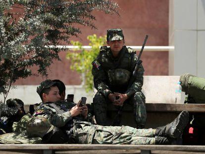 Soldados ecuatorianos toman un descanso a las puertas de la Asamblea Nacional. En vídeo, el país vuelve a la normalidad tras la derogación del 'paquetazo'.