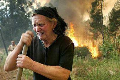 Una mujer llora ante las llamas que amenazan el pueblo de Outeiro, distrito de Viseu, el pasado martes.
