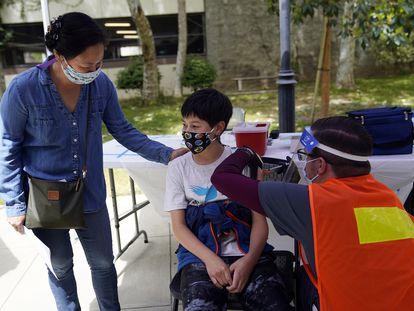 Colin Sweeney, de 12 años, recibe una inyección de la vacuna Pfizer mientras su madre Nicole le da una palmada en el hombro en la Primera Iglesia Bautista de Pasadena en Pasadena, California.