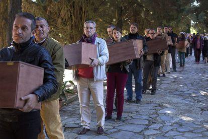 Un grupo de personas traslada restos de víctimas del franquismo exhumadas el pasado año en Cazalla de la Sierra (Sevilla).