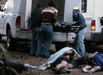 Los forenses de la policía mexicana cargan en camiones los cuerpos de seis hombres tiroteados hoy en Cuernavaca, en el norte de México.