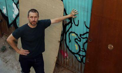 Carlos García frente al muro tras el que se encuentra el solar en el que se encontraba su casa que le expropiaron y derribaron hace cuatro años en Lavapiés