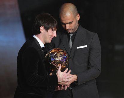 El futbolista argentino del Barcelona, Lionel Messi, recibe el Balón de Oro de las manos de su entrenador, Pep Guardiola.