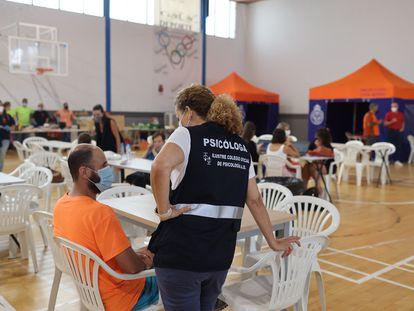 La psicóloga Alicia Doña asiste a uno de los 1.600 evacuados en el incendio de Sierra Bermeja (Málaga), acogidos en un pabellón de Ronda