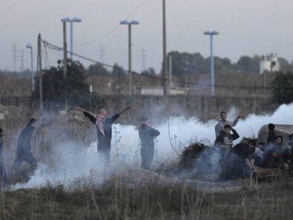 Manifestantes palestinos se ocultan de los gases lacrimógenos lanzados por las tropas israelíes durante los enfrentamientos en la frontera con Gaza, este sábado.