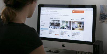 Una joven consulta una pagina web de anuncios de pisos de alquiler.