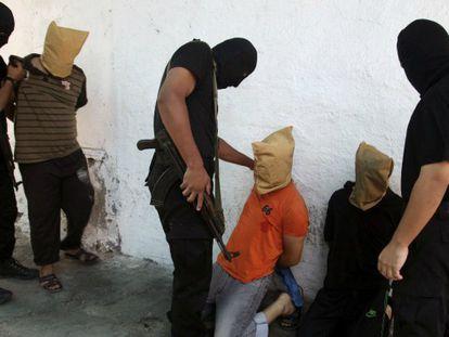 Milicianos de Hamás rodean a tres hombres acusados de colaborar con Israel / Foto y vídeo de Reuters