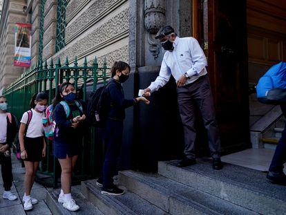 Alumnos de Buenos Aires hacen fila para que les tomen la temperatura antes del ingreso a la escuela.