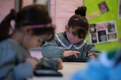 Niños de preescolar usan sus tabletas durante una clase en una escuela pública de Montevideo, en medio de la pandemia del nuevo coronavirus covid-19, el 11 de agosto de 2020.