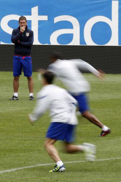 Simeone observa a sus jugadores durante el entrenamiento de esta mañana