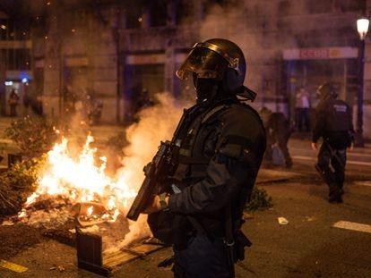 Un policía junto a una maceta incendiada por los manifestantes que protestaron el viernes por la noche en Barcelona contra el toque de queda.