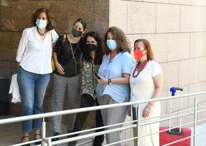 Carla Antonelli, segunda por la derecha, posa para una foto mientras abandona con su maleta la Asamblea de Madrid, este lunes.