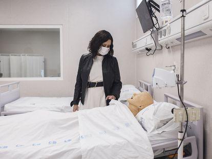 La presidenta de la Comunidad de Madrid, Isabel Díaz Ayuso, observa un maniquí que simula a un paciente durante su visita al hospital 12 de Octubre.