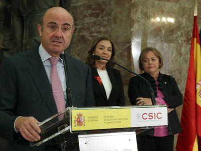 El ministro de Economía, Industria y Competitividad, Luis de Guindos, durante su intervención en el acto de toma posesión de la nueva presidenta del Consejo Superior de Investigaciones Científicas (CSIC), Rosa Menéndez (d), junto a la secretaria de Estado de I+D+i, Carmen Vela.