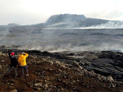 Dos personas observan el cráter apagado del volcán islandés Fagradalsfjall.