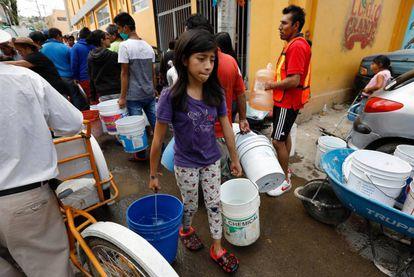 Una niña carga agua para su casa en Ciudad de México.