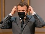 French President Emmanuel Macron adjusts his protective mask during the traditional Lily of the Valley ceremony at the Elysee palace in Paris, France May 1, 2021. Ludovic Marin/Pool via REUTERS