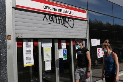 Dos jóvenes pasan ante una ofician de empleo este martes en Madrid.