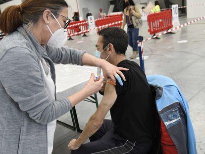 Una sanitaria vacuna a un hombre en el Instituto Ferial de Vigo (Ifevi), en Pontevedra, Galicia (España), a 13 de marzo de 2021.