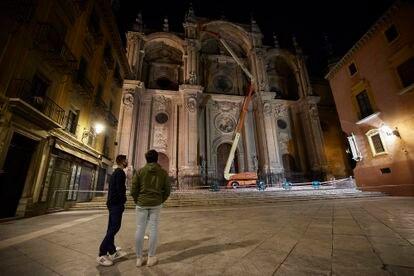 Operarios revisan, en la noche del viernes, la fachada de la catedral de Granada tras desprenderse algunos fragmentos.